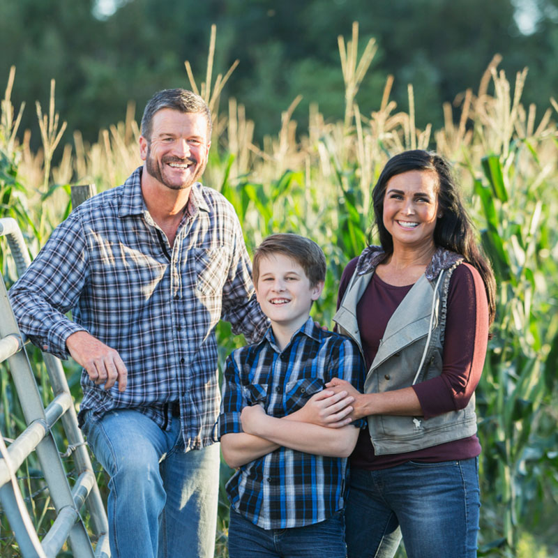 Farm family standing in front of a corn field